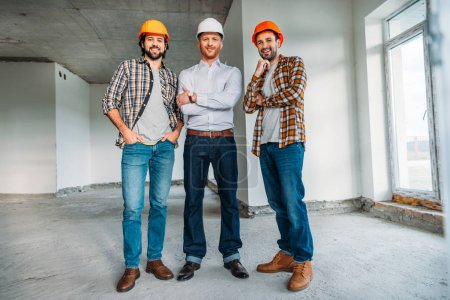 group of architects inside of constructing building looking at camera