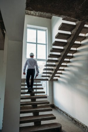 Photo for Rear view of architect going upstairs inside of building house - Royalty Free Image