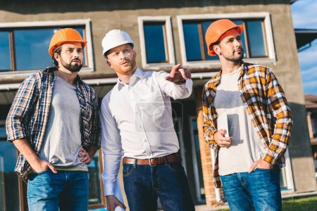 group of handsome architects having conversation and pointing somewhere