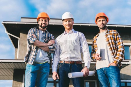 group of handsome architects in front of construction site
