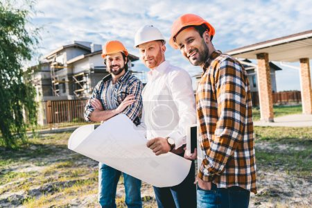 group of architects with blueprint in garden at construction site
