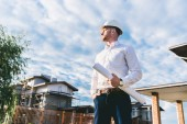 bottom view of handsome architect in white shirt with blueprint standing at yard in front of building house and looking away