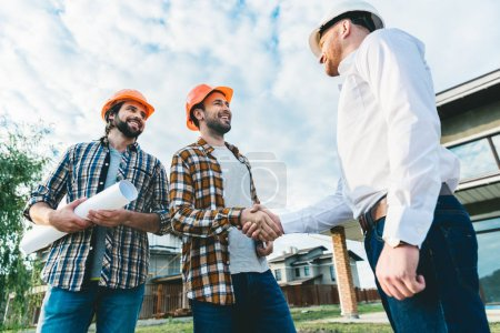 group of architects having conversation in garden at construction site