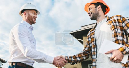 bottom view of smiling architects shaking hands in front of construction site