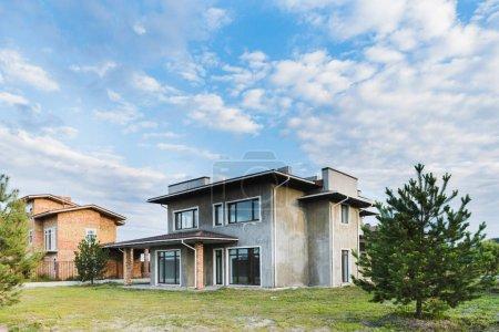 bâtiments contemporains inachevés avec yards verts nuageux avec sapins sur le premier plan