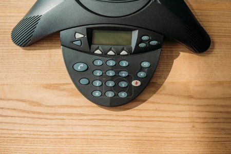 top view of speakerphone on wooden table at office