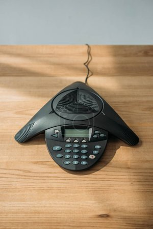 high angle view of speakerphone on wooden table at office