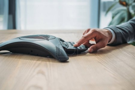 side view cropped shot of businessman pushing button of conference phone at workplace