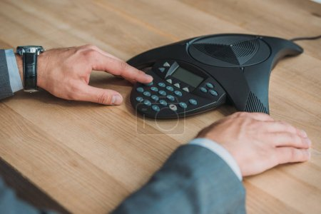 cropped shot of businessman using conference phone at workplace