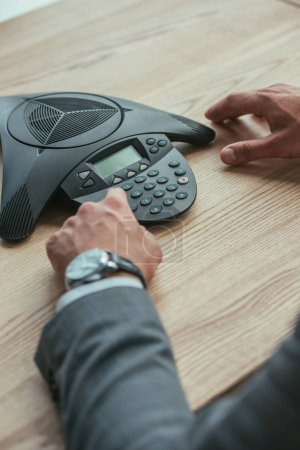 cropped shot of businessman pushing button of conference phone at workplace in office