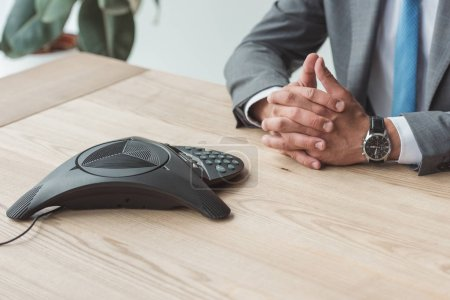 cropped shot of businessman sitting at workplace with conference phone