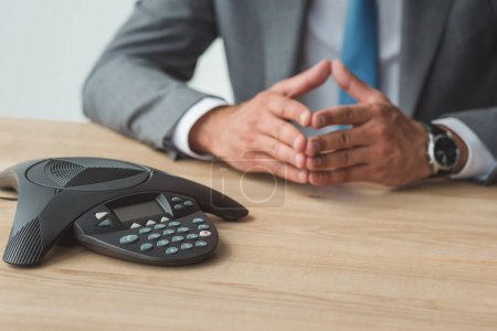 cropped shot of businessman sitting in front of speakerphone and having conversation at office