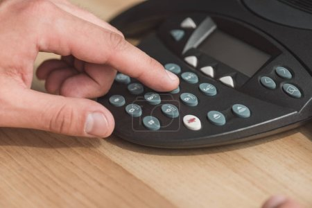 cropped shot of man pushing button of conference phone on wooden table