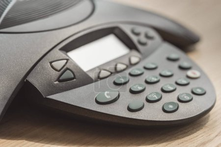 Photo for Partial of speakerphone on wooden table at office - Royalty Free Image