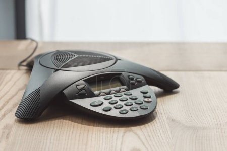 close-up shot of modern conference phone on wooden table at office
