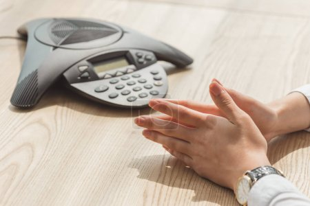 cropped shot of businesswoman sitting in front of conference phone on wooden table