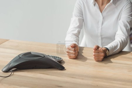cropped shot of businesswoman in white shirt sitting in front of conference phone on table and making fists
