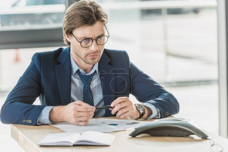 serious young businessman with various documents on table looking at conference