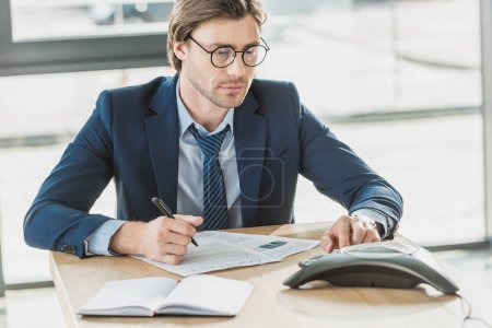 handsome young businessman with lot of paperwork using conference phone at office