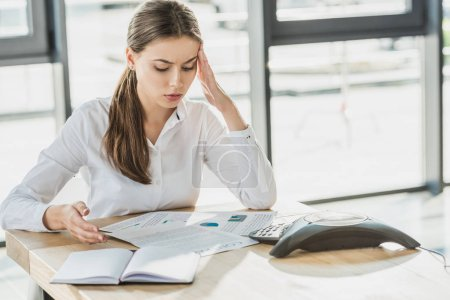 overworked young businesswoman with headache doing paperwork at office