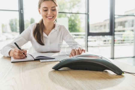 young happy businesswoman doing paperwork and pushing button of conference phone on table at office
