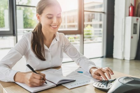 young smiling businesswoman doing paperwork and pushing button of conference phone on table at office
