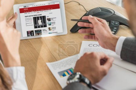 Photo for Cropped shot of businessman and businesswoman looking at tablet, bbc website on screen - Royalty Free Image