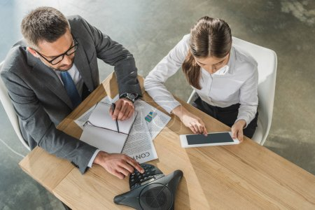 high angle view of successful businessman and businesswoman with tablet and speakerphone working together at modern office