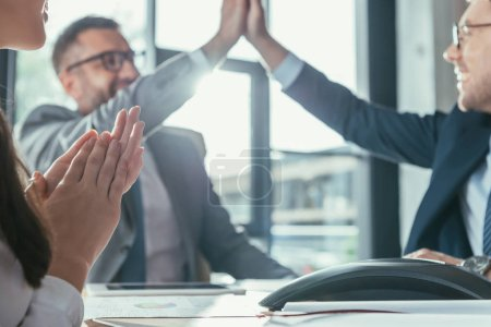 Photo for Successful business people giving high five during meeting at modern office - Royalty Free Image
