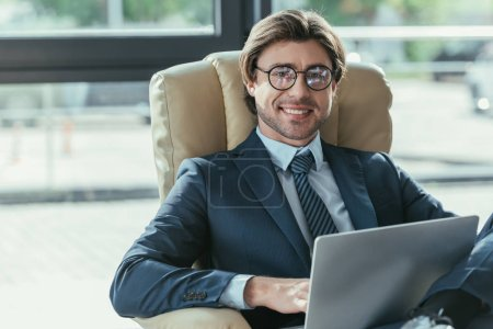 handsome smiling businessman sitting using laptop in armchair and looking at camera