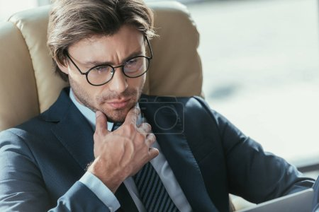 Photo for Attractive  thoughtful businessman sitting in armchair and looking away at modern office - Royalty Free Image