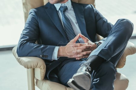 cropped shot of businessman relaxing on luxury armchair at modern office