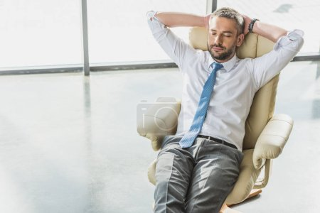 high angle view of handsome businessman relaxing on luxury armchair at modern office