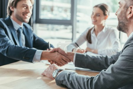 business people shaking hands during meeting at modern office