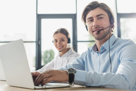 Photo for Male and female call center managers working together at modern office and looking at camera - Royalty Free Image