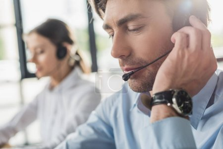 Photo for Handsome call center manager in headphones with mike sitting at workplace while his colleague sitting on background - Royalty Free Image