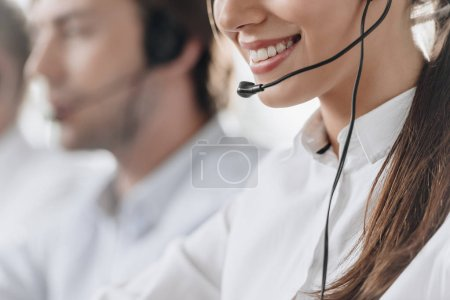 Foto de Recortada la foto de la sonriente joven llamada Subdirectora de centro de trabajo con colegas - Imagen libre de derechos