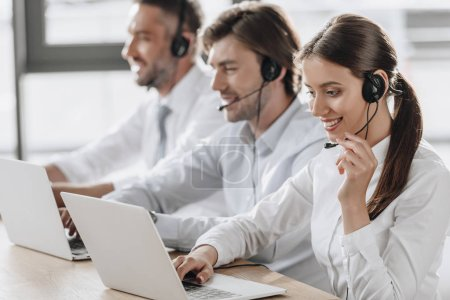 smiling call center managers in white shirts working together while sitting in row at modern office