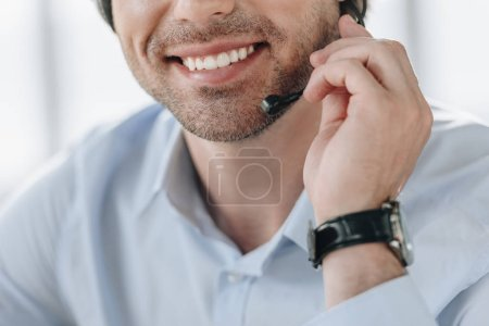 cropped shot of smiling support hotline worker holding microphone