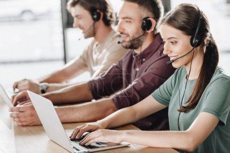 Foto de Feliz equipo de gerentes de centro de llamadas trabajando juntos, sentados en fila en la oficina moderna - Imagen libre de derechos