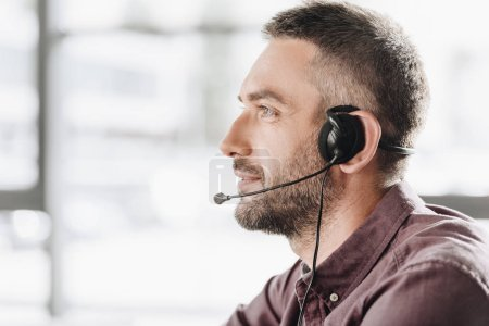 side view of handsome call center worker in headphones with microphone