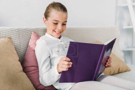 Photo pour Adorable petit livre de lecture d'enfant tout en se relaxant sur le canapé à la maison - image libre de droit