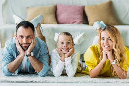 happy young family lying on floor at home and looking at camera