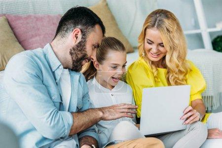 Photo pour Souriante jeune famille avec ordinateur portable ensemble à la maison - image libre de droit