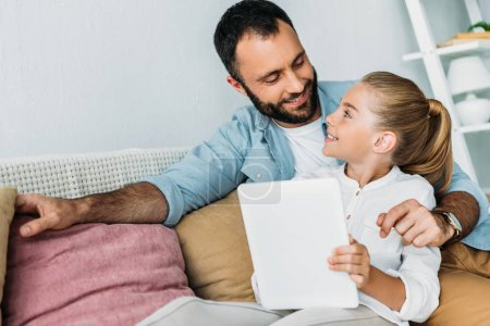 Photo for Father and daughter using tablet together while sitting on couch at home - Royalty Free Image