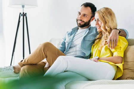 beautiful couple relaxing on couch and watching tv at home