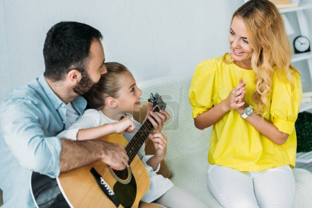Photo for Father and daughter playing guitar for mother at home while she clapping - Royalty Free Image
