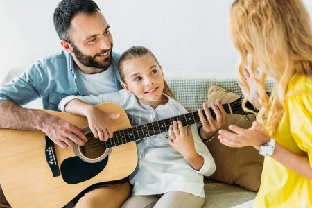 father and daughter playing guitar for mother at home