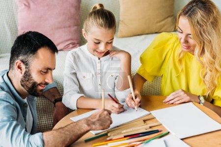 Photo pour Heureux jeune famille réunissant avec des crayons de couleur à la maison - image libre de droit