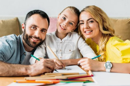 happy young family drawing with color pencils together and looking at camera